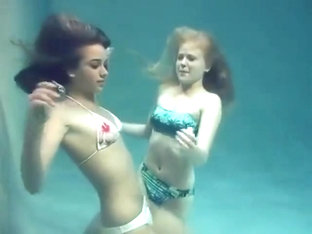 Two girls breath holding and posing underwater